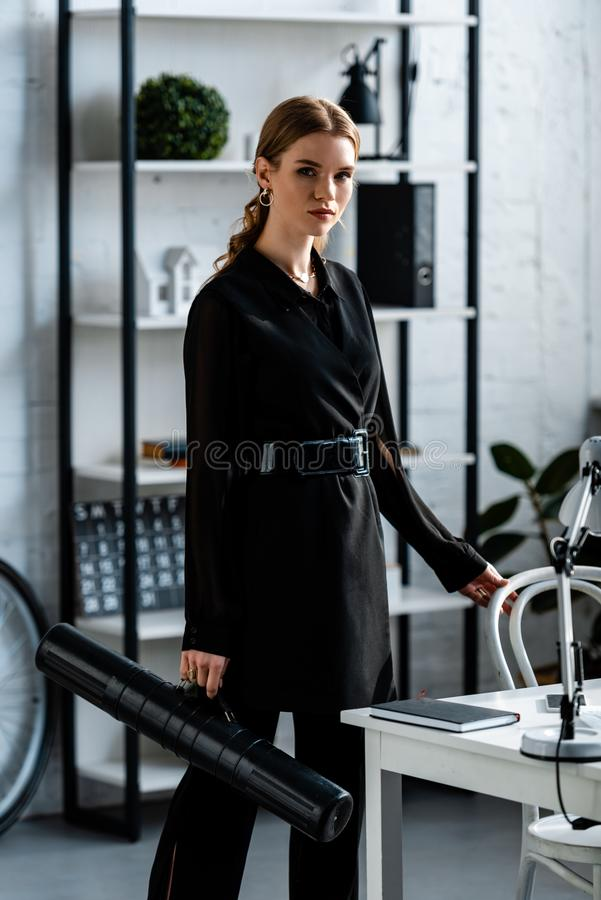 Beautiful businesswoman in black clothes standing at office and looking. At camera royalty free stock photos
