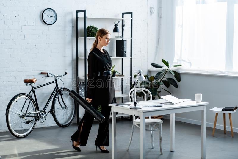Beautiful businesswoman in black clothes standing at office and looking. At notebook royalty free stock photo