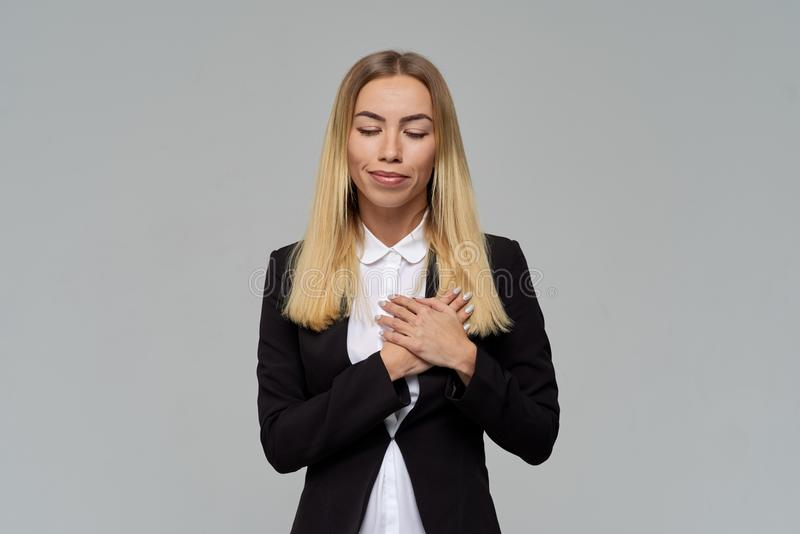 Beautiful businesswoman blonde closed her eyes and smiles, folding her hands on her chest. stock photo