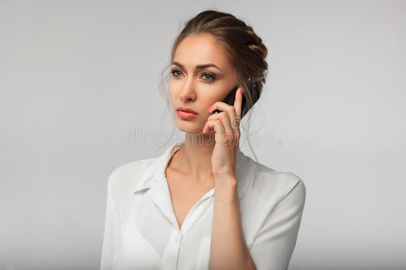 Beautiful businesswoman with a cell phone in hands. serious conversation. business portrait royalty free stock photos