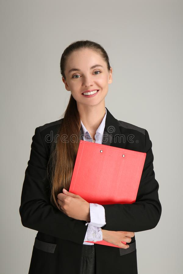 Beautiful businesswoman with clipboard on grey background stock images