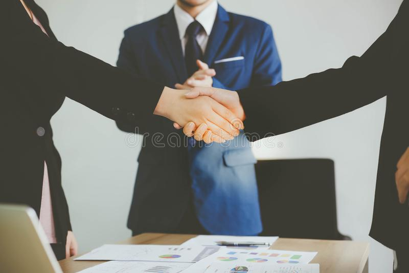 Beautiful businesswoman and customer woman are dealing the contract by handing shake and handsome businessman is clapping hand royalty free stock photo