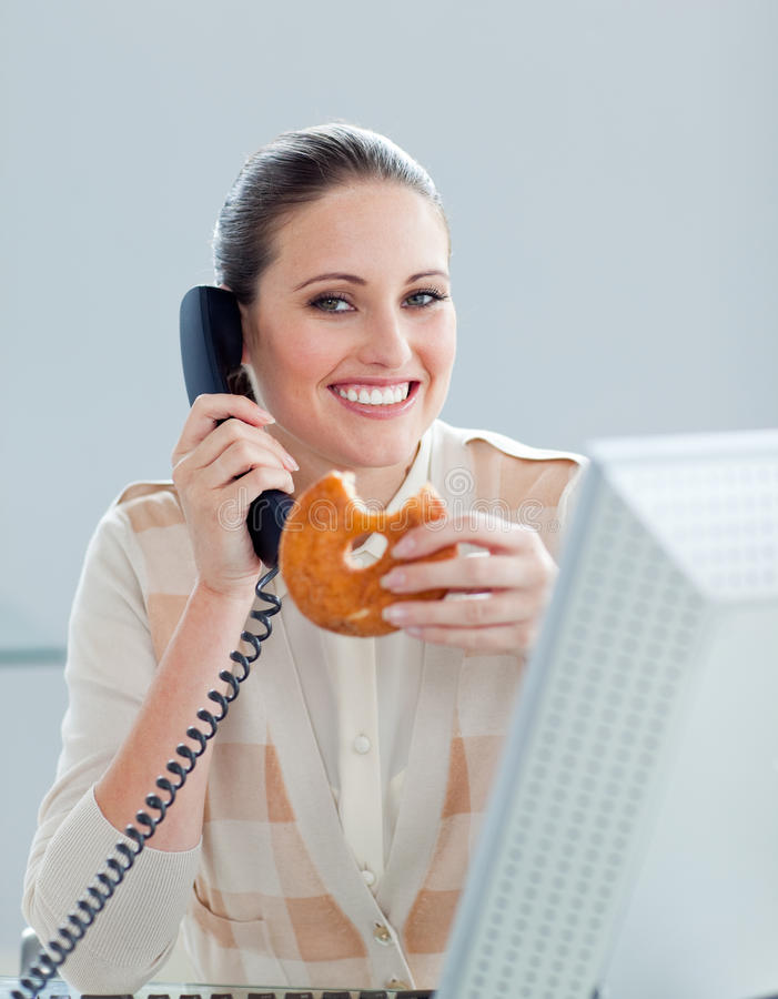 Beautiful businesswoman eating a donuts stock photography