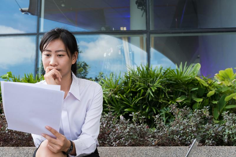 businesswoman with financial graph sitting outside office building. young asian woman analyzing investment charts outdoors. royalty free stock photos