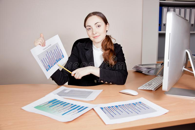 Beautiful businesswoman with financial report at office stock photo