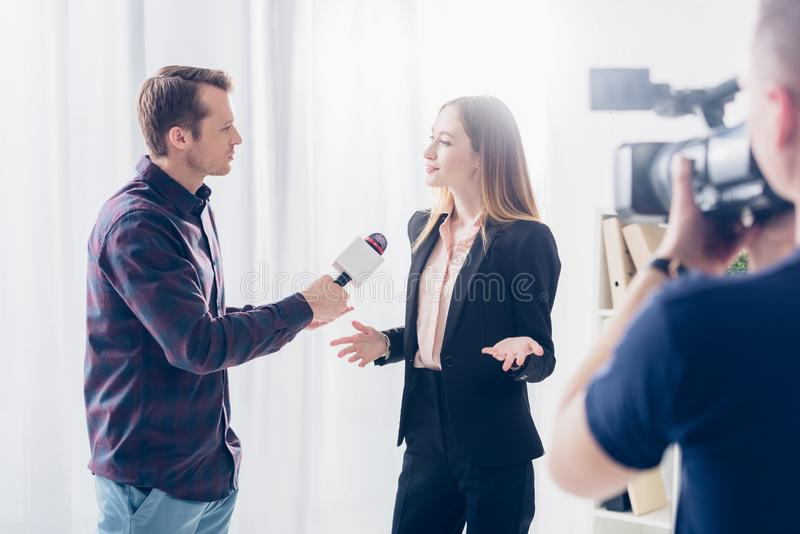 Beautiful businesswoman in formal wear giving interview to journalist and gesturing. In office royalty free stock photography