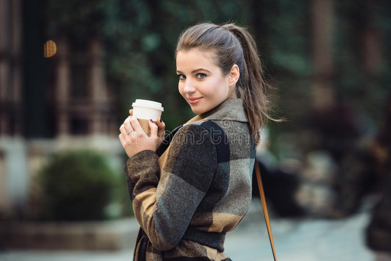 Beautiful businesswoman holding coffee cup and walking on city street to the work at spring time. stock photos