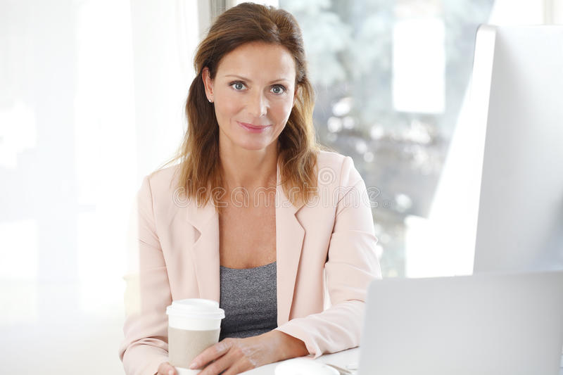 Beautiful businesswoman. Portrait of an attractive businesswoman sitting at her desk in an office while has a coffee break stock image