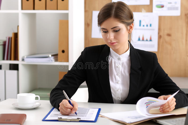 Beautiful businesswoman sit at workplace in office. Work with papers portrait. Serious business, exchange market, job offer, analytics researc, excellent royalty free stock photo