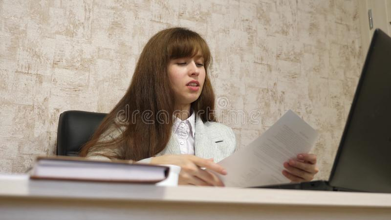 Beautiful businesswoman sitting in chair in office and working online on laptop and with paper documents. young woman stock photos