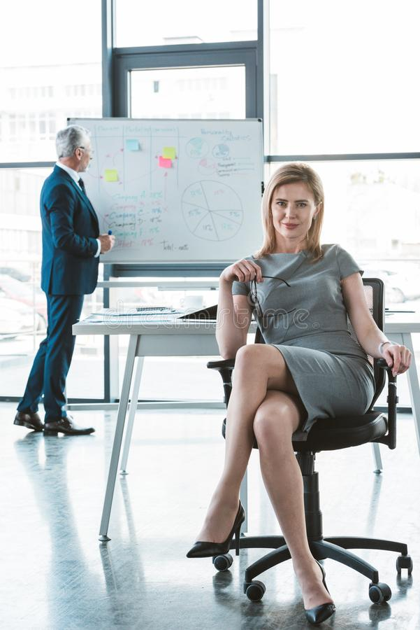 Beautiful businesswoman sitting on chair and smiling at camera while senior businessman standing. Near whiteboard behind stock photos