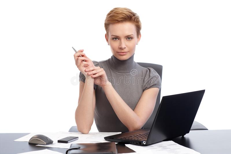 Beautiful businesswoman sitting at desk stock images