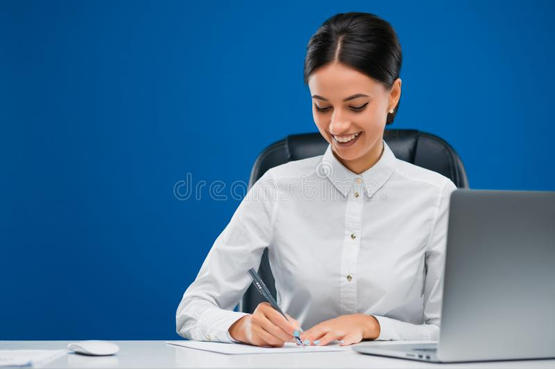 Beautiful businesswoman sitting at her desk before a laptop writing with enthusiasm her ideas on a sheet of paper, isolated on. Beautiful, young businesswoman royalty free stock photography