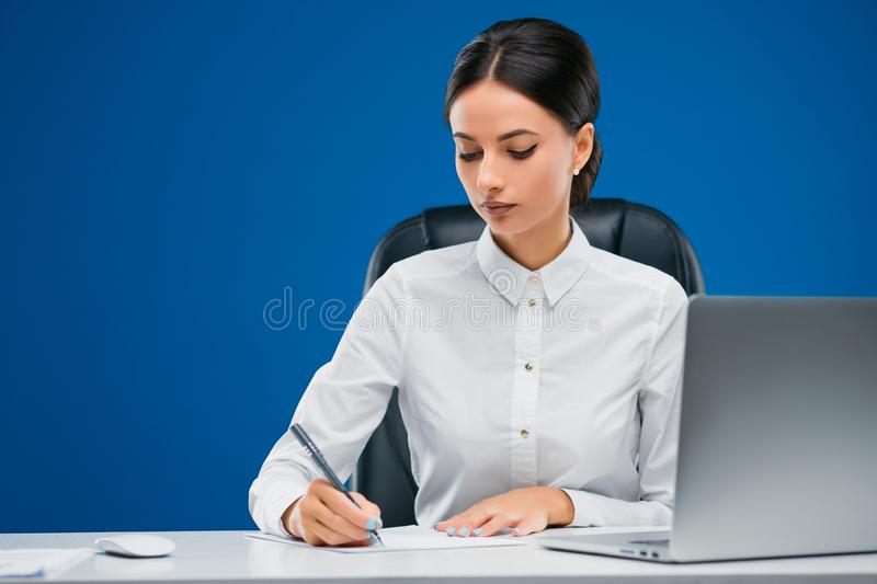 Beautiful businesswoman sitting at her desk before a laptop writing her ideas on a sheet of paper, isolated on blue background. Beautiful, young businesswoman stock image
