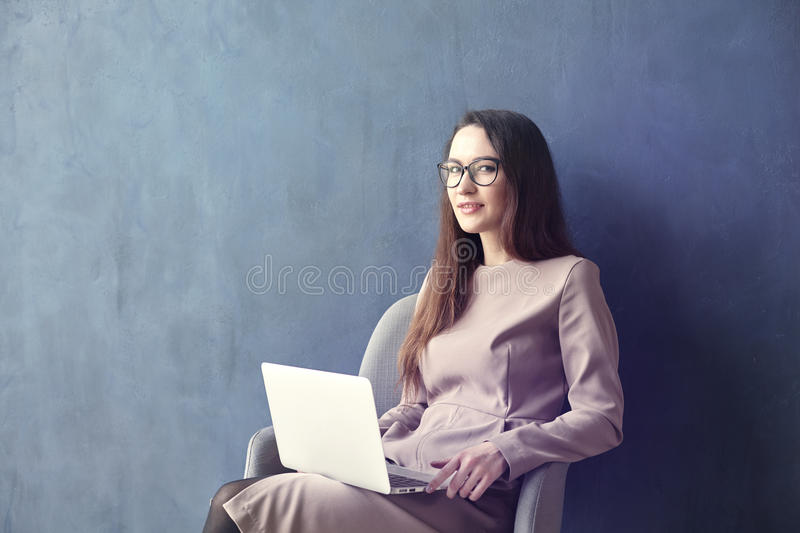 Beautiful businesswoman sitting in loft office using laptop on knees. Look and smile. Dark blue wall background, day light. stock photography