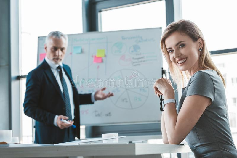 Beautiful businesswoman smiling at camera while senior businessman standing. At whiteboard behind royalty free stock image