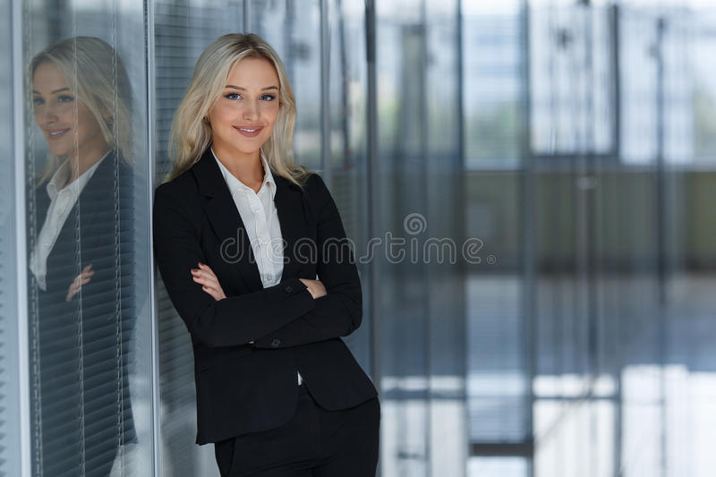 Beautiful businesswoman smiling with folded arms in office. stock images