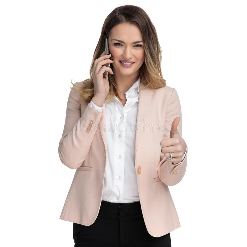 Beautiful businesswoman speaks on the phone and makes ok sign royalty free stock image