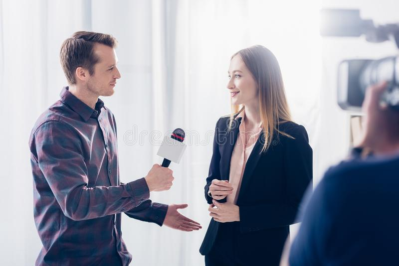 Beautiful businesswoman in suit giving interview to handsome journalist. In office royalty free stock photography
