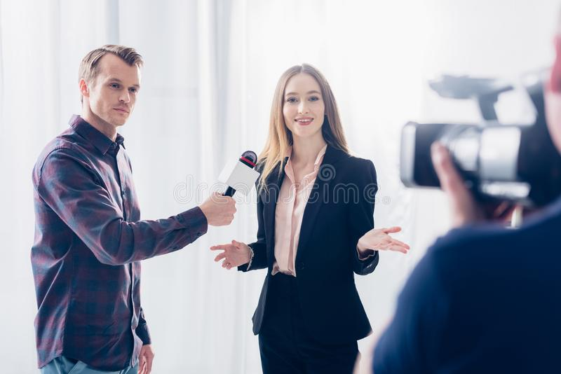 Beautiful businesswoman in suit giving interview to journalist and gesturing. In office royalty free stock photos