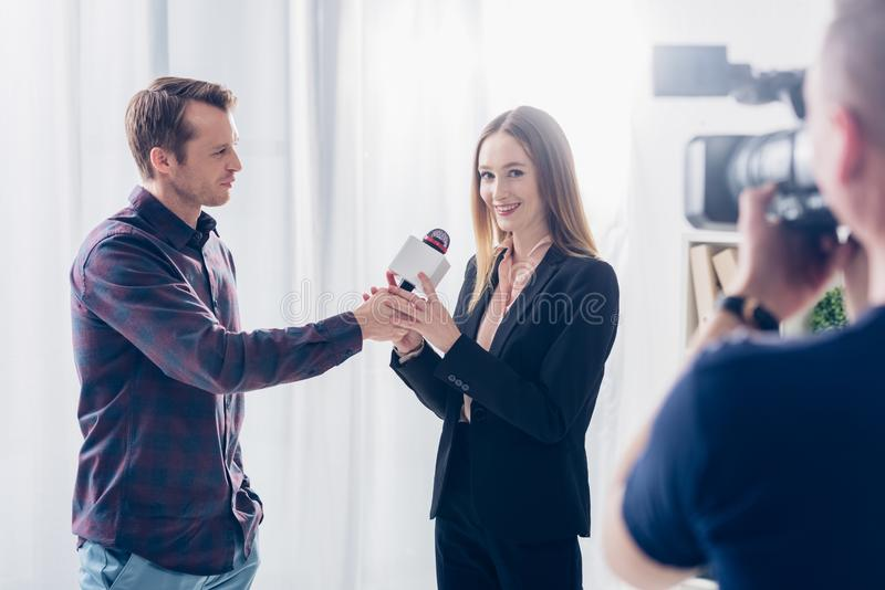Beautiful businesswoman in suit giving interview to journalist, holding microphone and looking at camera. In office stock image