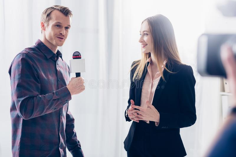 Beautiful businesswoman in suit giving interview to journalist. In office stock image