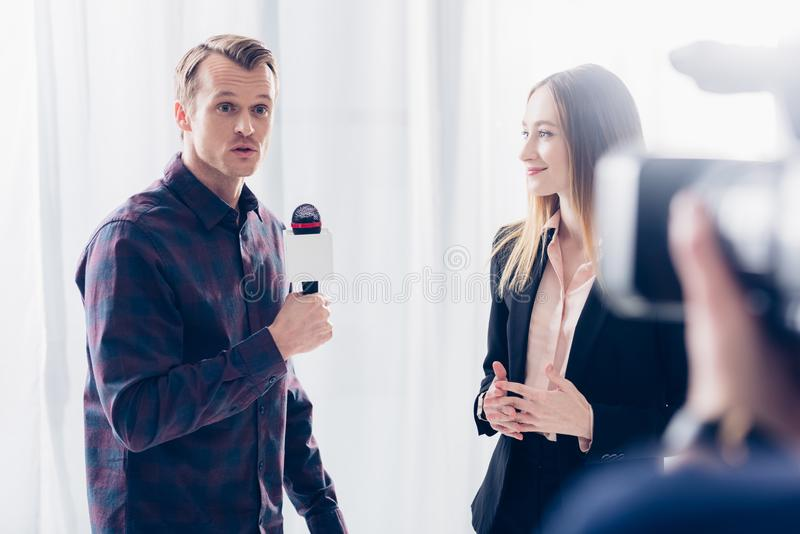 Beautiful businesswoman in suit giving interview to surprised journalist. In office stock photos
