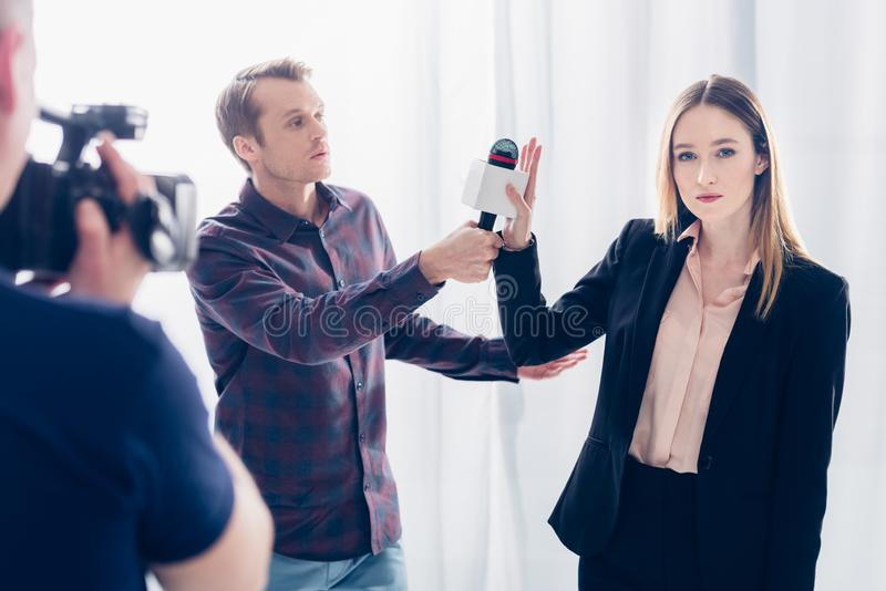 Beautiful businesswoman in suit rejecting giving interview to journalist. In office royalty free stock image