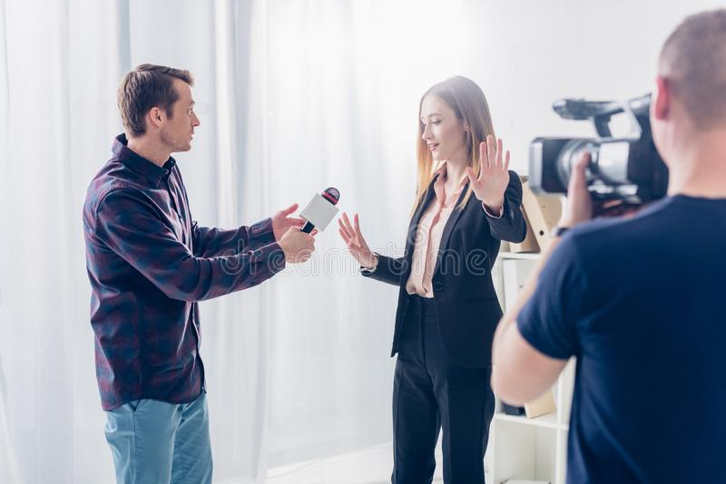 Beautiful businesswoman in suit rejecting giving interview to journalist and showing stop sing to cameraman. In office royalty free stock image