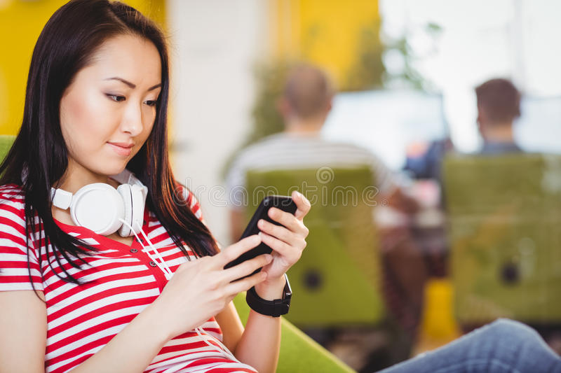 Beautiful businesswoman using cellphone at creative office. Beautiful young businesswoman using cellphone at creative office stock photography