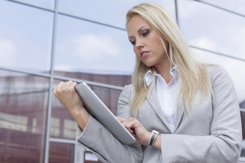 Beautiful businesswoman using digital tablet against office building stock photography
