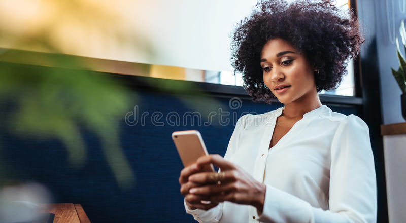 Beautiful businesswoman using smart phone in office stock photos
