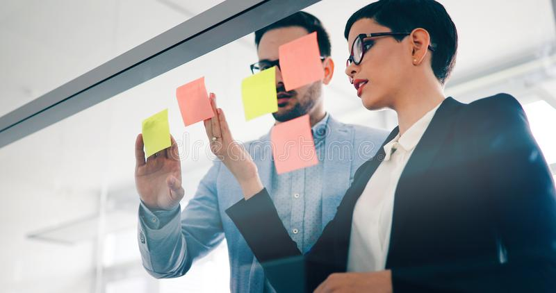 Businesswoman using sticky notes at office to plan project royalty free stock photos