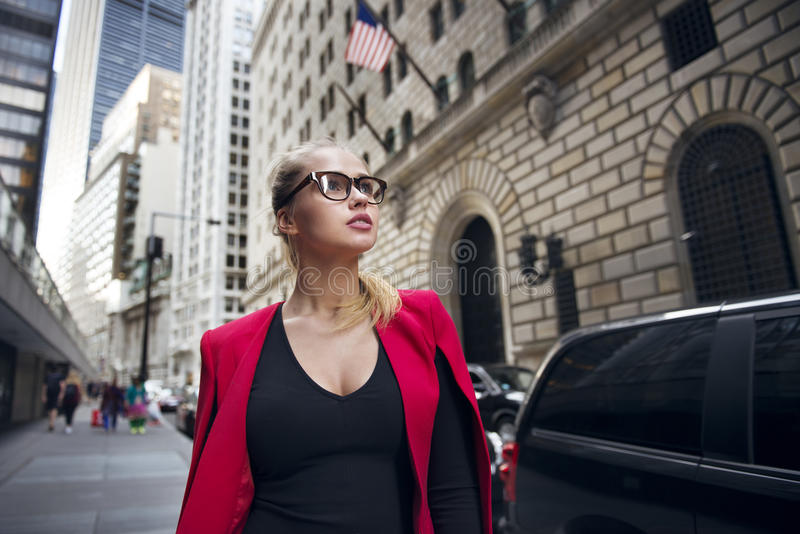 Beautiful businesswoman walking for break on Wall Street Financial district in New York City. Concept photo of business people royalty free stock photography