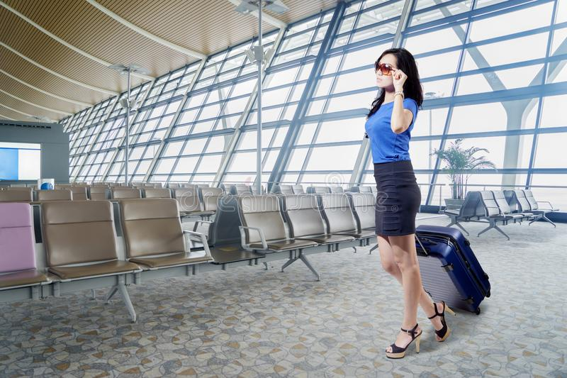 Beautiful businesswoman walks in the airport terminal stock image