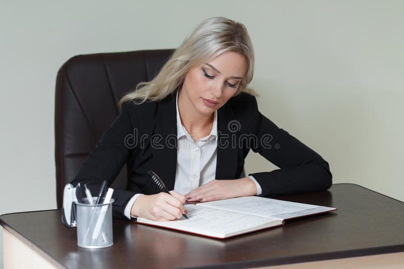 Beautiful businesswoman writing in a notebook in office. royalty free stock photography