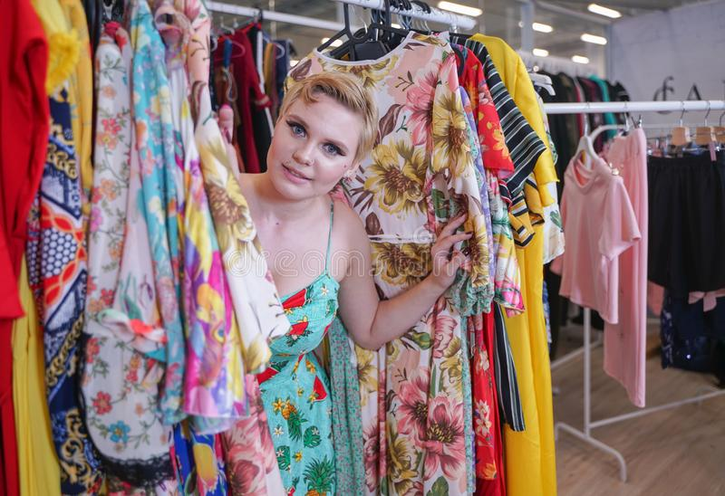 Beautiful buxom girl in a fashionable dress walking in the store and chooses new clothes, looking at trendy costumes on hangers in. The Mall alone. blonde plus royalty free stock image