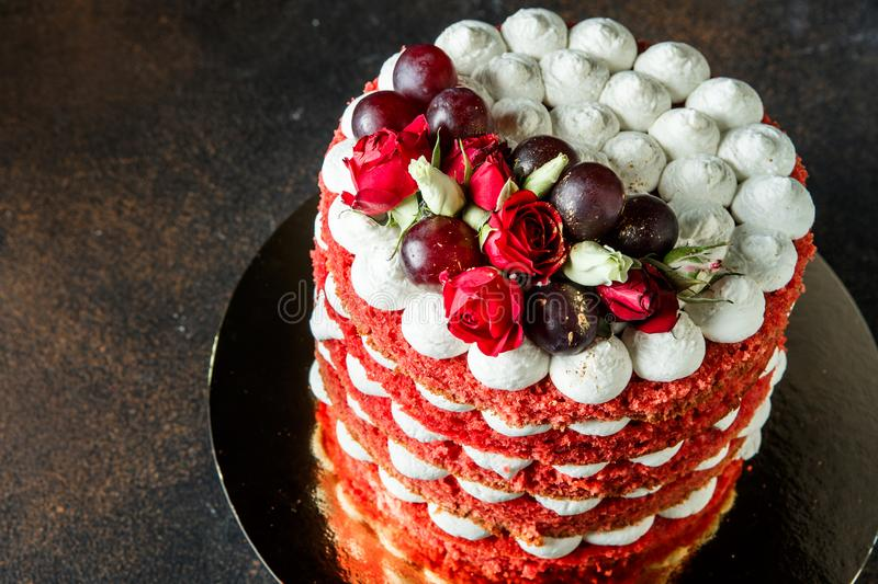 Beautiful cake with bizet, grapes and roses. Beautiful multi-layer cake with white airy bizet, red grapes and red and white roses royalty free stock photography