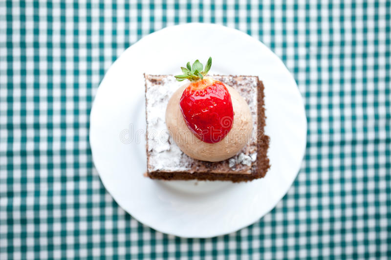 Beautiful cake with strawberry. On plaid fabric royalty free stock photos