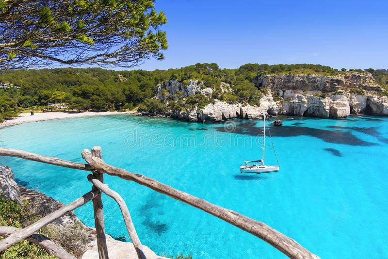 Beautiful Cala Macarella beach, Menorca island, Spain. Sailing boat in a bay. Summer fun, enjoying life, yachting, travel and acti royalty free stock photography