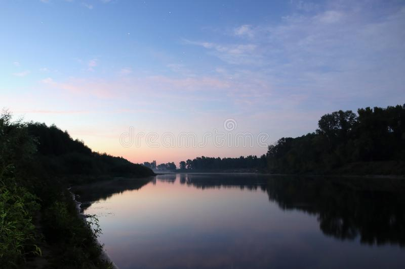 Beautiful calm sunrise dawn with stars in sky by the river with reflection on mirror water stock photo