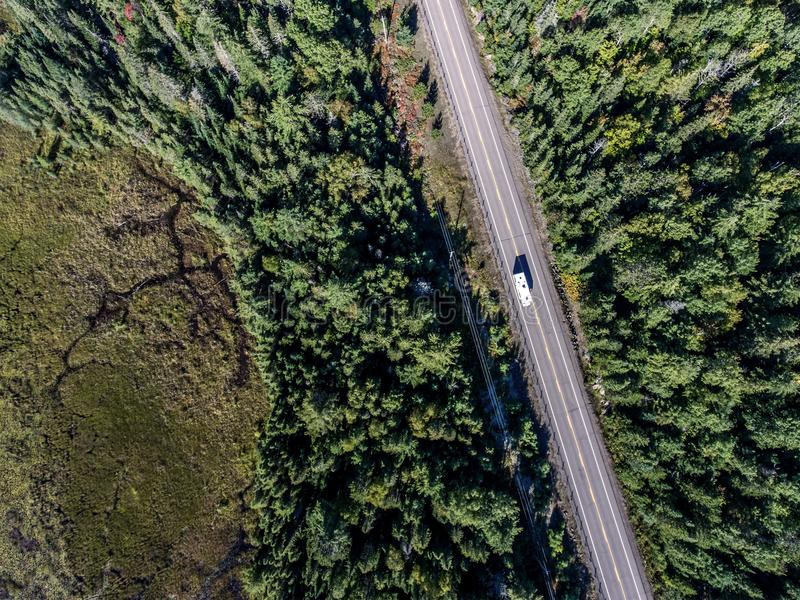 Beautiful Canada camper bus driving on road endless pine tree forest with lakes moor land aerial view travel background stock photography