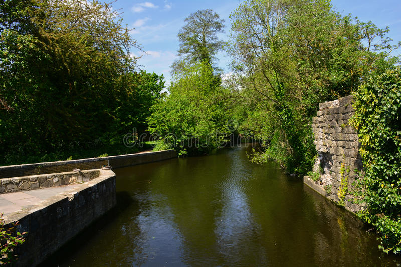 Beautiful Canal scene near ruined abbey wall in summer, Waltham Abbey, UK. Waltham Abbey is a market town of about 20,400 people in Epping Forest District in the stock photo