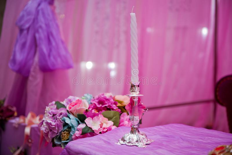 White decorative candles pink backgrounds . Beautiful candle on pink background . Candle in candlestick burning . Retro Candelabra royalty free stock photo