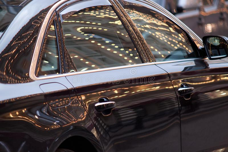 Bright glare on the surface of the car. Beautiful car with reflection of illumination on the surface stock photos