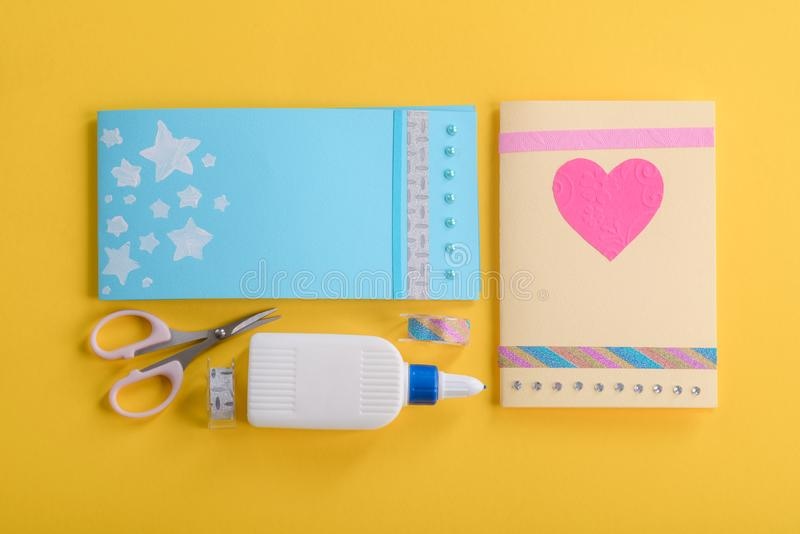 Beautiful cards to gift. Flat lay photo of little girl`s workplace, finished craft and tools on the table. Elementary school project stock images