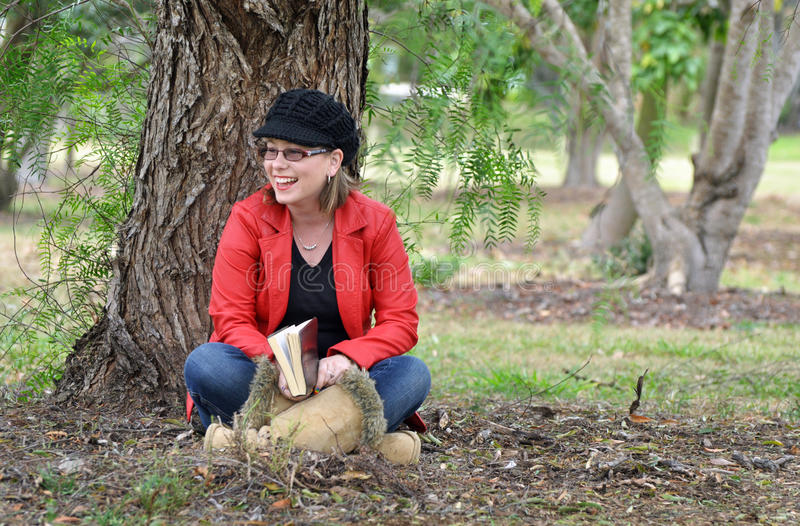 Beautiful carefree happy laughing young woman outdoors under tree. A photograph of a gorgeous young girl sitting under a huge old weeping willow tree outdoor in stock image