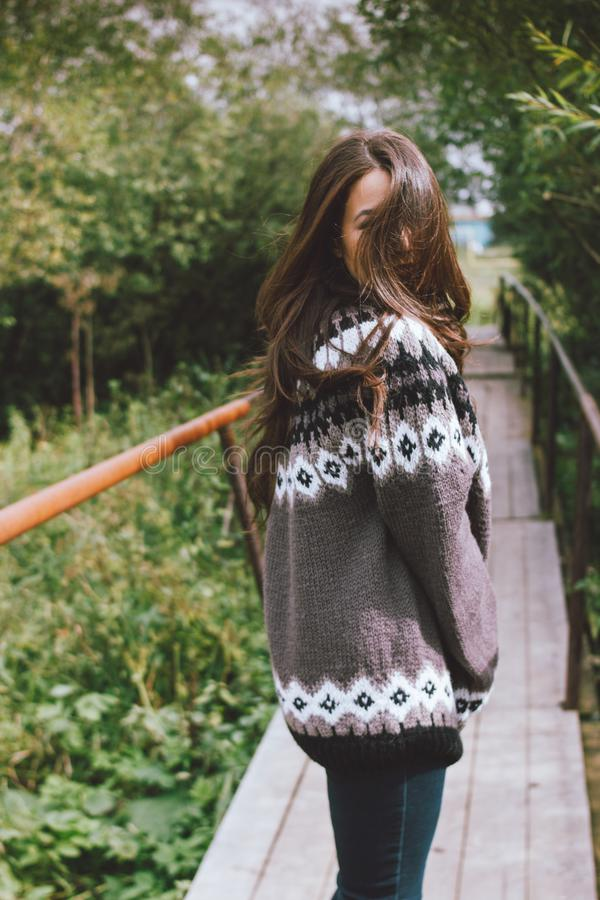 Beautiful carefree long hair asian girl in knitted nordic sweater in autumn nature park royalty free stock images