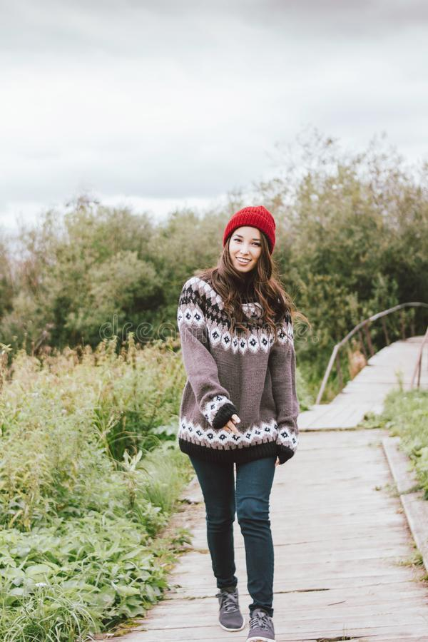 Beautiful carefree long hair asian girl in the red hat and knitted nordic sweater in autumn nature park stock photos