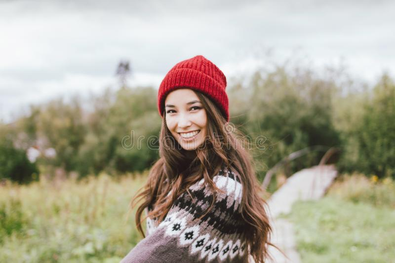 Beautiful carefree long hair asian girl in the red hat and knitted nordic sweater in autumn nature park royalty free stock image